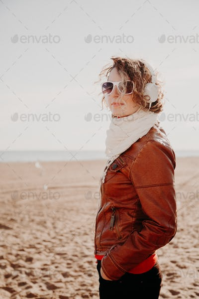 Young woman in a white headphones listening to music at the beach in summer day