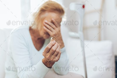 Heartbroken elderly woman holding a wedding ring