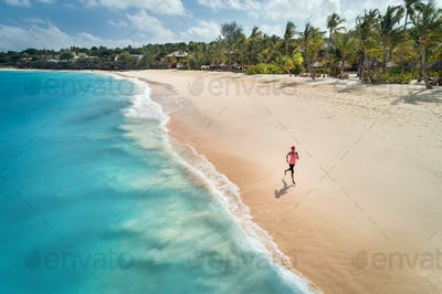 Aerial view of the running young woman on the sandy beach