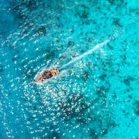 Aerial view of the fishing boat in transparent blue water