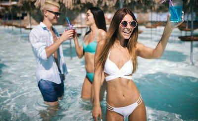 Group of happy friends having fun dancing at swimming pool outdoors