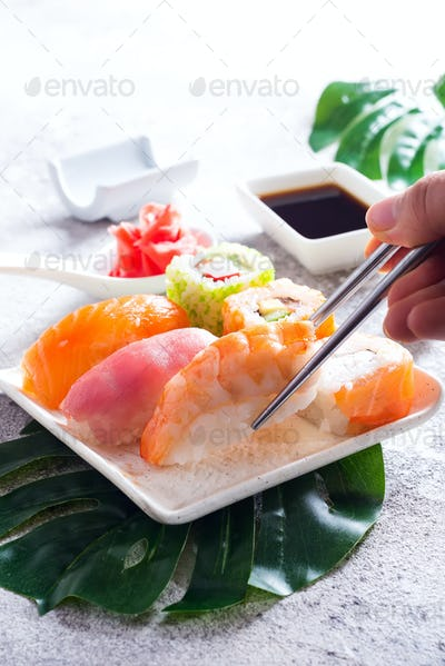 Various sushi on ceramic plate with metal Korean sticks and hand on light stone background with