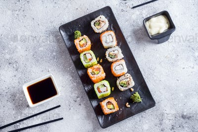 Various Fresh and delicious sushi set on black slate with metal and slate sticks, sauce on light