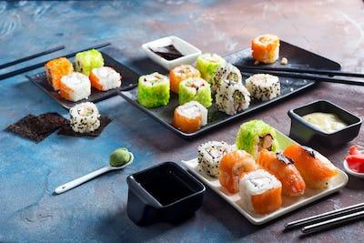 Traditional Japanese food- sushi, rolls, chopsticks, soy sauce on color stone background. Sushi menu