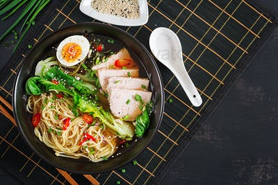 Miso Ramen Asian noodles with egg, pork and pak choi cabbage in bowl on dark background.