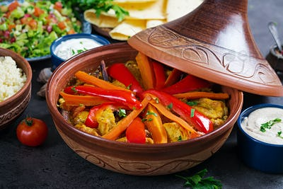 Moroccan food. Traditional tajine dishes, couscous  and fresh salad  on rustic wooden table.