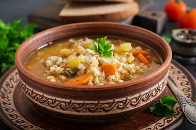 Barley soup with carrots, tomato, celery and meat on a dark background.