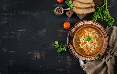 Barley soup with carrots, tomato, celery and meat on a dark background. Top view.