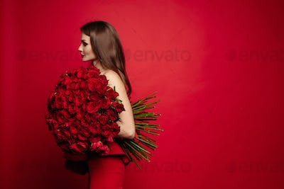 Gorgeous woman in red dress keeping bouquet of roses