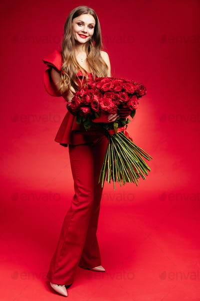 Happy young brunette in red dress holding big bunch of red roses