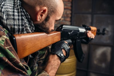 Cruel terrorist aiming from a rifle closeup