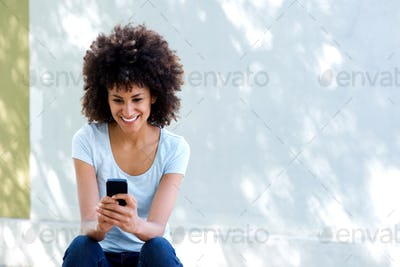 Happy woman with curly hair holding cellphone