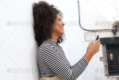 Side of happy woman with curly hair and smart phone