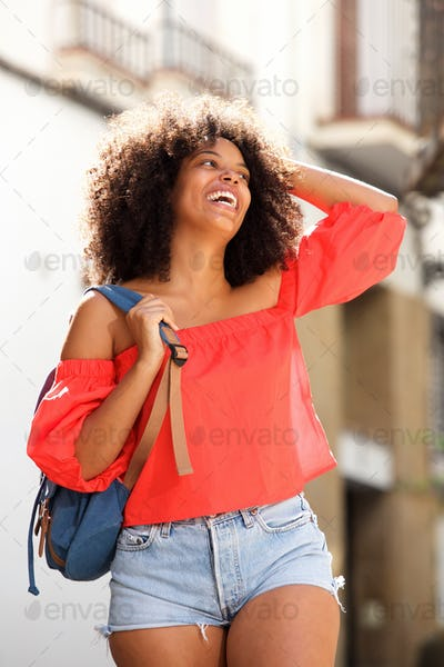 Beautiful black woman laughing outside with backpack