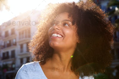 Close up smiling african american woman outside in city