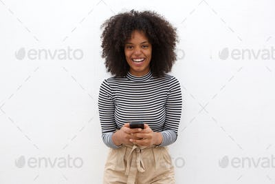 Laughing african american woman holding smart phone