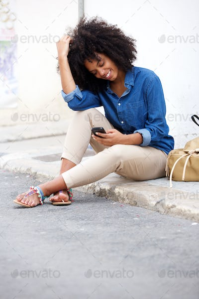 Bllack woman sitting by street smiling with mobile phone