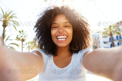 Selfie of laughing black woman outside with curly hair