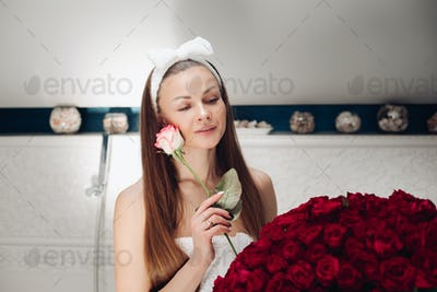 Girl with long hair sitting on bath after morning shower