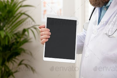 Adult male doctor showing a digital image or report on a tablet