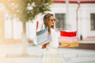 Happy model in white look and sunglasses holding shopping bags u