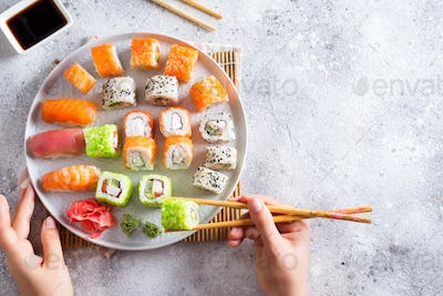 Various Fresh and delicious sushi set on white slate , hand with wooden sticks, sauce on light stone