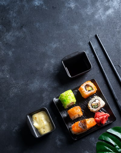 Various Fresh and delicious sushi set on black slate with slate sticks, sauce and nori on black