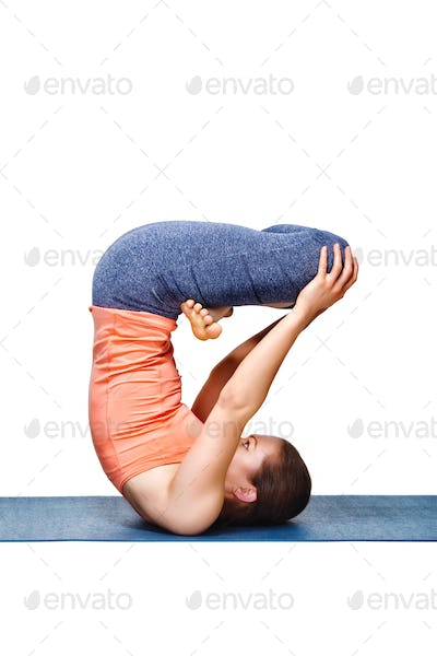 Sporty fit yogini woman practices inverted yoga asana