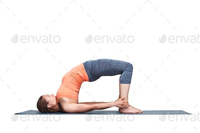 Beautiful sporty fit yogi girl practices yoga asana setu bandhas