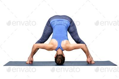 Woman practices Ashtanga Vinyasa yoga asana Prasarita padottanasana