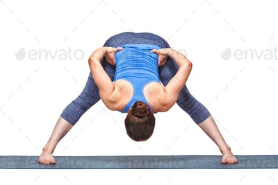 Sporty fit woman doing yoga asana Prasarita padottanasana B