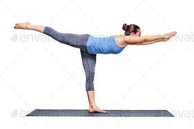 Sporty fit woman practices yoga asana utthita Virabhadrasana 3