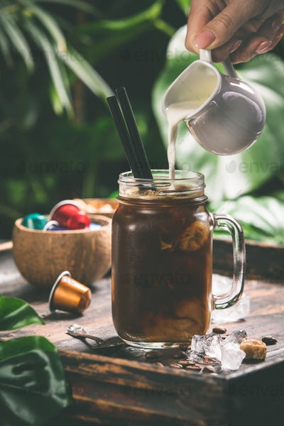 Iced coffee and tropical background, close up
