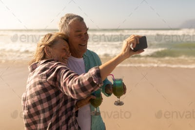 Senior couple taking selfie with mobile phone while having cocktail drink on the beach