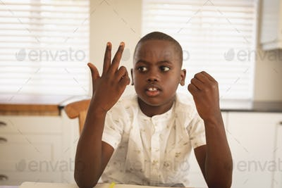 Front view of thoughtful African American boy doing homework on dining table in kitchen at home