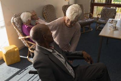Front view of senior woman talking with disable senior man at nursing home