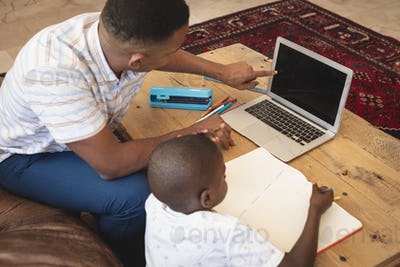 Father helping his son with homework on laptop at table in a comfortable home