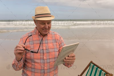 Front view of active senior man using digital tablet on the beach. They seem happy. he wears a hat
