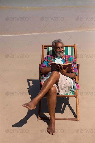 High angle view of senior man relaxing on sun lounger and reading a book on beach in the sunshine