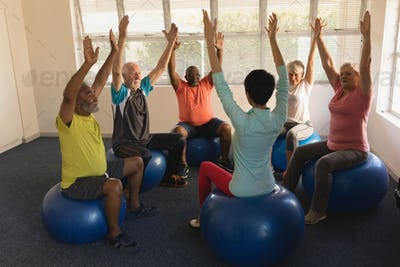 Front view of female trainer training senior people in performing exercise ball at home