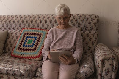Front view of senior woman concentrated and using digital tablet on sofa at home