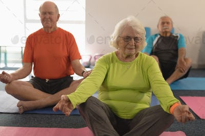 Front view of senior people doing yoga in position yoga in fitness studio