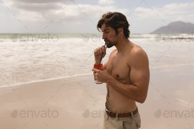 Rear view of shirtless young man drinking cocktail on beach in the sunshine