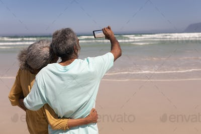Rear view of senior couple taking selfie with mobile phone on beach in the sunshine