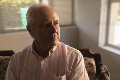 Closeup of thoughtful senior man relaxing in living room at nursing home
