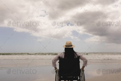 Rear view of disabled young woman with hat sitting on wheelchair at beach