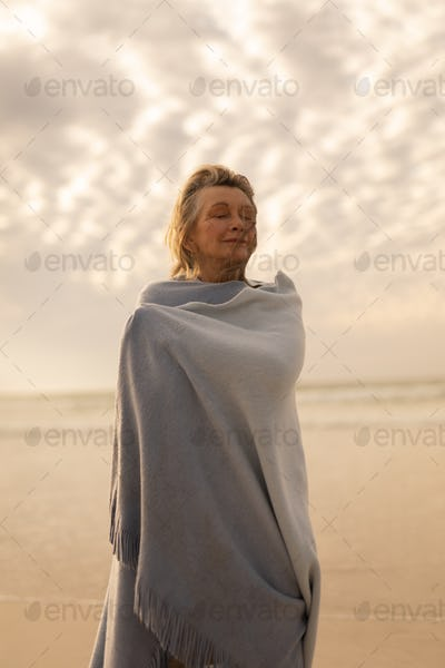Senior woman wrapped in a shawl with closed eyes standing on the beach