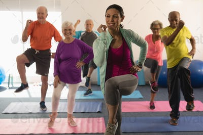 Front view of young female trainer assisting senior people in fitness studio