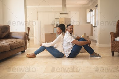 Happy couple sitting on floor back to back and looking at camera in a comfortable home