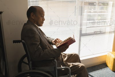 Side view of disable senior man sitting on wheelchair and reading a book at home
